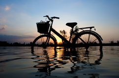 Bicycle silhouette standing in sunset. Bicycle silhouette standing in the water at sunset Royalty Free Stock Image
