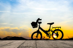 Bicycle silhouette with sun set. Bicycle silhouette with sun set wih wooden board Royalty Free Stock Image