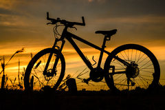 Bicycle silhouette on a sunset. The Bicycle silhouette on a sunset middle of a prairie, Thailand royalty free stock images