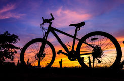 Bicycle silhouette on a sunset. Background surrounded by meadows stock photography