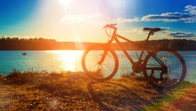 Bicycle silhouette at sunset lake, in autumn, beautiful landscape. Bicycle silhouette at sunset lake, in autumn, beautiful royalty free stock photos