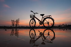 Bicycle silhouette on a sunset. Silhouette bicycle with reflection on sunset Royalty Free Stock Image