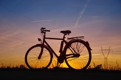 Bicycle silhouette on sunset. Retro bicycle silhouette on sunset with energy pole in background stock image