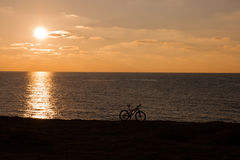 Bicycle silhouette at sunset sea Stock Photos