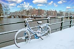 Bicycle in snowy Amsterdam in the Netherlands. Bicycle in Amsterdam the Netherlands covered in snow Royalty Free Stock Images