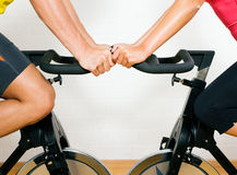Bicycle spinning in the gym. Couple (only limbs to be seen) training on bicycles in the gym Royalty Free Stock Image