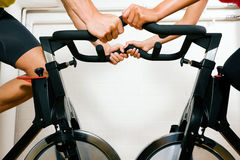 Bicycle spinning in the gym. Couple (only limbs to be seen) training on bicycles in the gym Stock Image
