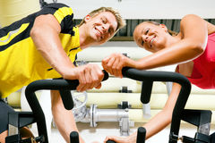 Bicycle spinning in the gym. Couple exercising by spinning on stationary bicycles in the gym Royalty Free Stock Image