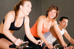Bicycle Spinning in gym. Three people spinning on stationary bicycles in the gym, focus on the smiling woman in the middle Stock Photos