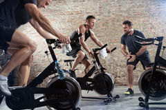 Bicycle spinning with personal trainer Royalty Free Stock Photography