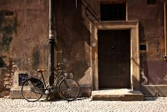 Bicycle standing next to an old wall and door Royalty Free Stock Images