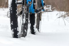 A bicycle standing in the snow close up. Snow flakes floating on dark off-road tires. Winter weather in the field. stock image