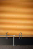 Bicycle stands in front of corrugated iron wall Stock Photography