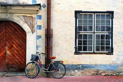 Bicycle stands at the gate in an old house with a square window. Latvia, Riga. Bicycle standing on a red stone blocks at the wooden gate in an old house with a Stock Image