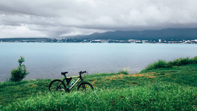 A bicycle stands on a green lawn of the sea coast with a view of the mountain range concept of active recreation and healthy lifes Stock Photo