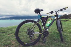 A bicycle stands on a green lawn of the sea coast with a view of the mountain range concept of active recreation and healthy lifes Royalty Free Stock Photography