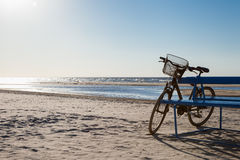 Bicycle stands near bench on beach Stock Photos