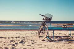 Bicycle stands near bench on beach against sea. Stock Photo