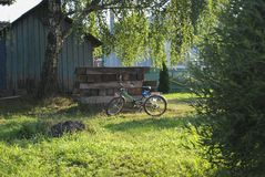 A bicycle stands near a village house. Rural landscape. Rural transport Stock Photos