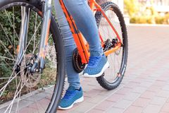 Bicycle steering wheel with speed selector, cables and brakes, speed sprocket. The girl put her foot on the bicycle pedal. A bicycle element on a street Royalty Free Stock Photo