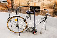 Bicycle with a stolen front wheel is chained to a bicycle parking lot. stock photography