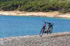 Bicycle on stony beach, Kamenjak peninsula, Adriatic Sea, Premantura, Croatia. Bicycle stands on stony beach, Kamenjak peninsula by the Adriatic Sea, Premantura royalty free stock photo