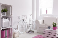 Bicycle storing in room. White female bicycle storing in bright spacious room Royalty Free Stock Images