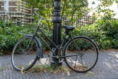 Bicycle in the street, chained to a lamp post stock image