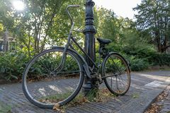 Bicycle in the street, chained to a lamp post stock images