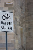 Bicycle Street sign with a black bicycle close to a gray wall Stock Image