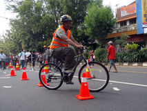 Bicycle stunt riding. Residents are following the race Stunt riding a bicycle on a street in the city of Solo, Central Java, Indonesia Royalty Free Stock Images