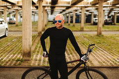 Bicycle style man in black sportswear. And sunglasses on urban parking Stock Images