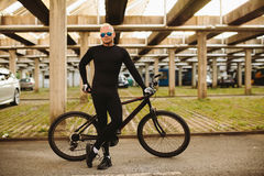 Bicycle style man in black sportswear. And sunglasses on urban parking Stock Photography