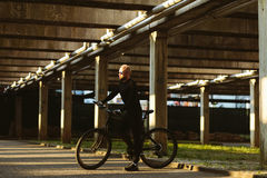 Bicycle style man in black sportswear. And sunglasses in urban street Royalty Free Stock Photography