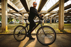 Bicycle style man in black sportswear. And sunglasses in urban street Royalty Free Stock Photo