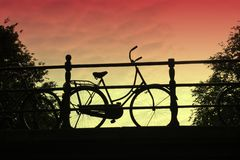Bicycle at sunset, an Amsterdam icon. A bicycle on a bridge, silhouetted against a sunset sky.  Common mode of transport in Amsterdam, Holland Stock Image