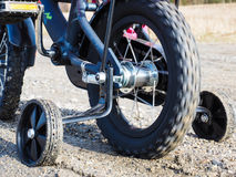 Bicycle with supporting wheels stuck in loose gravel Royalty Free Stock Photo