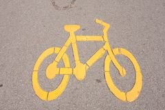 Bicycle symbol. Yellow bike symbol. On the background in the park Stock Photography