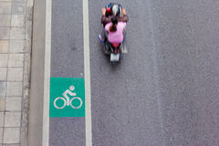 Bicycle symbol on city street with motion blur of motorcycle Royalty Free Stock Photo