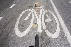 Bicycle sign. Bicycle symbol on city street on top view with bicycle wheels royalty free stock images