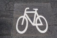 Bicycle symbol on gray asphalt stock photos