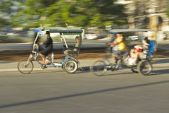 Bicycle taxis speeding through the streets with sunlight on it in Havana, Cuba Royalty Free Stock Image