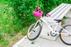 Bicycle for teenage girl with pink protective helmet. In the Park royalty free stock image