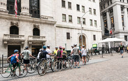 Bicycle tour pauses in front of New York Stock Exchange. New York, NY, June 16, 2015: Group on bicycle tour pauses in front of New York Stock Exchange in Lower stock photo