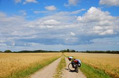 Bicycle Touring In The Countryside. A touring bike, loaded up with panniers and gear, on a dirt track in Denmark - part of the national cycle route stock photo