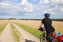 Bicycle Touring In The Countryside. A man on a touring bike, loaded up with panniers and gear, on a dirt track in Denmark - part of the national cycle route stock photos