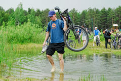 Bicycle tourist fords the stream. Tyumen Royalty Free Stock Images