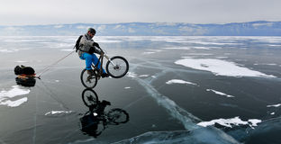 Bicycle tourist on the frozen lake. Bicycle tourist on the bike with sledge riding on the rear wheel only and having fun on the frozen lake Royalty Free Stock Image