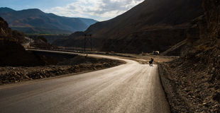 Bicycle tourist on the highway. Bicycle tourist on the mountain valley highway in evening light Royalty Free Stock Photos