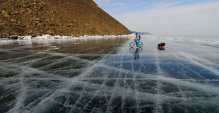 Bicycle tourist on the ice. Bicycle tourist riding on the surface of frozen lake with sledge stock photos